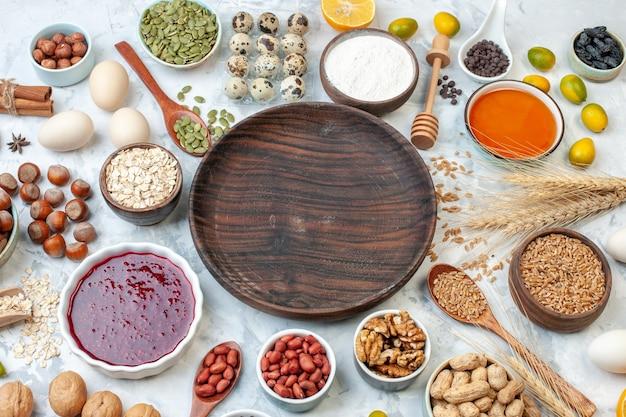 Placa de madeira redonda de vista superior com ovos de geleia, nozes e sementes diferentes na massa branca, açúcar cor doce, biscoito, nozes, bolo de fotos