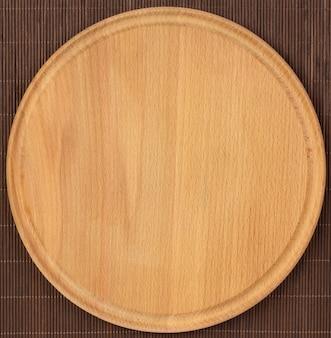 Placa de madeira redonda vazia com toalha de mesa.