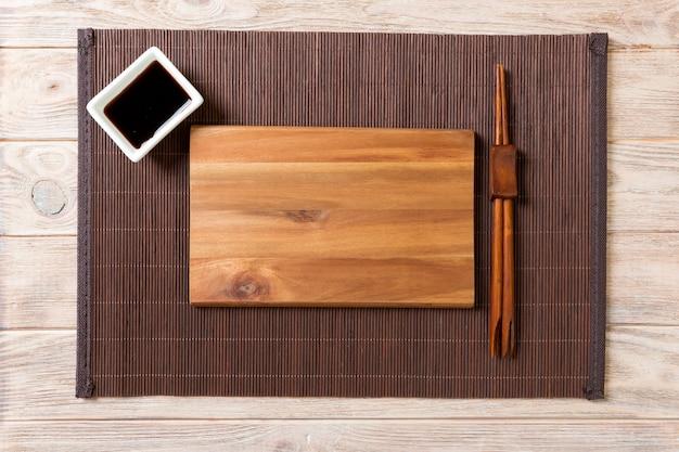 Placa de madeira retangular vazia com pauzinhos para sushi e molho de soja na madeira