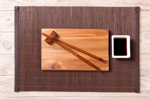 Placa de madeira retangular vazia para sushi com molho e pauzinhos na madeira
