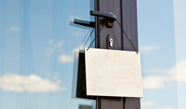 Placa de madeira sem texto pendurado na porta no café