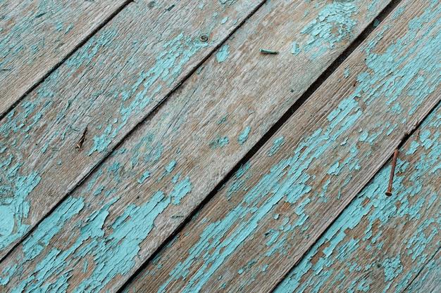 Placa de madeira turquesa velha com pregos enferrujados. fundo de textura vintage