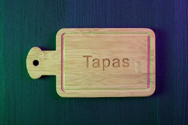 Placa de madeira vazia na mesa de madeira. tapa espanhola. copie o espaço e a vista superior