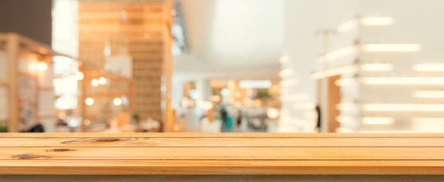 Placa de madeira vazia topo de mesa fundo desfocado. perspectiva mesa de madeira marrom sobre borrão no fundo da cafeteria. banner panorâmico - pode ser usado como maquete para exibição ou design de produtos de montagem.