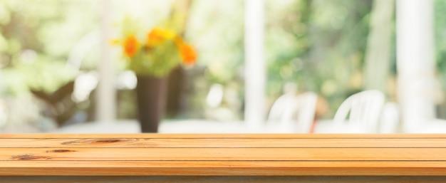 Placa de madeira vazio topo de mesa fundo borrado. tabela de madeira marrom da perspectiva sobre o borrão no fundo da cafetaria. bandeira panorâmica - pode ser usado mock para exibição de produtos de montagem ou design.