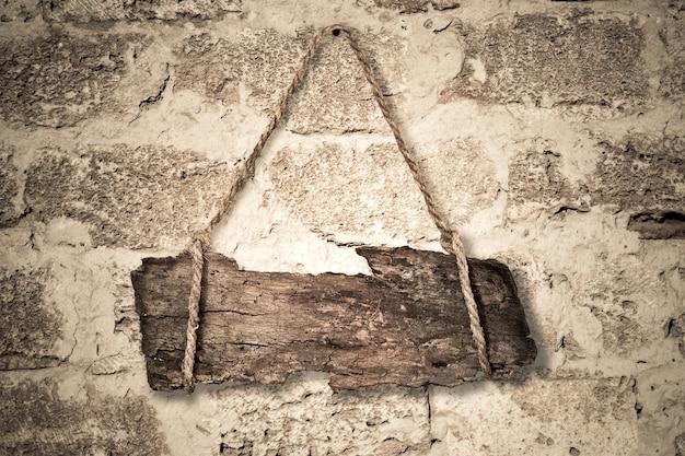 Placa de madeira velha pendurada em uma parede de pedra