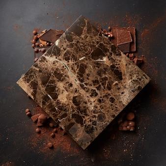 Placa de mármore para texto e pó de chocolate em parede preta