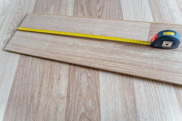 Placa de medição de piso de madeira laminado com fita métrica amarela para reconstrução e renovação de ambiente. fechar-se