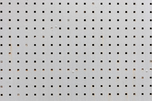 Placa de metal cinza com buracos negros quadrados