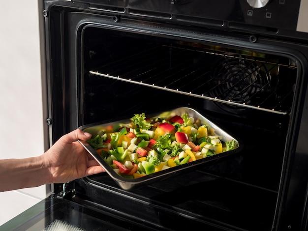 Placa de metal com legumes no forno