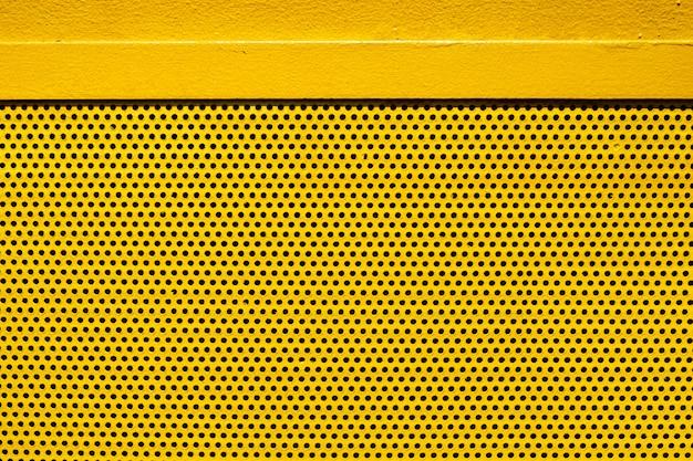 Placa de metal de cor amarela com muitos pequenos buracos circulares pontilha a textura para o fundo