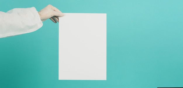 Placa de papel em branco à mão com luva de látex branca e terno de ppi em fundo verde menta ou azul tiffany.