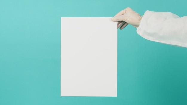 Placa de papel em branco na mão de uma mulher. ela usa luva de látex branca e terno de ppi em fundo verde menta ou azul tiffany.