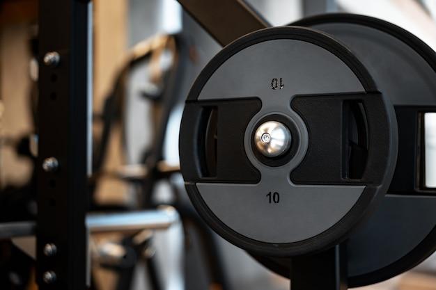 Placa de peso na barra de metal em uma academia