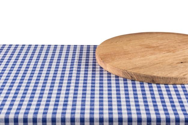 Placa de pizza de madeira vazia na toalha de mesa quadriculada azul.