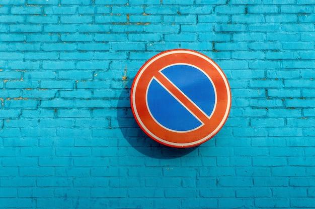 Placa de proibição de espera em parede de tijolo azul