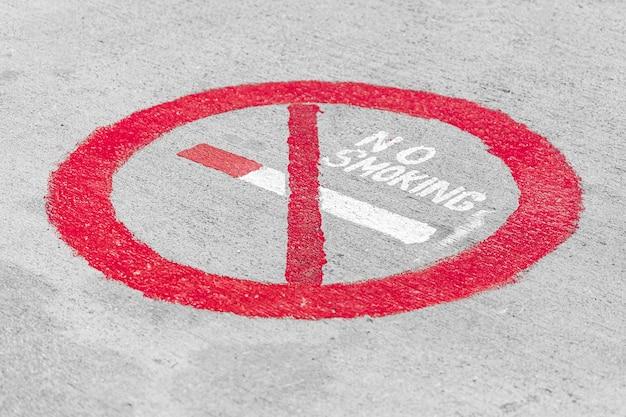 Placa de proibição de fumar com um cigarro riscado em um círculo vermelho pintado em uma parede branca