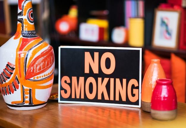 Placa de proibido fumar apoiada em cerâmica artesanal de cores vivas em uma loja, avisando que é uma zona proibida de fumar e que é proibido fumar no local
