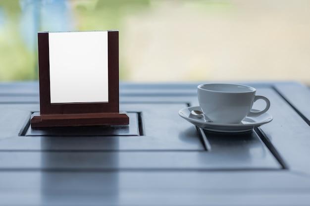 Placa de propaganda de maquete em branco na tela com uma xícara de café em uma mesa de café