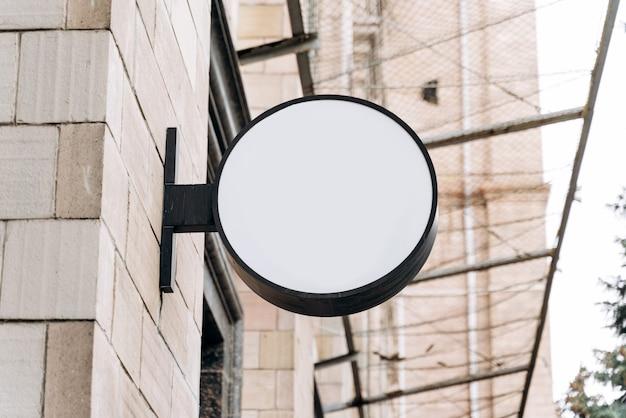 Placa de publicidade branca no prédio. maquete de uma placa redonda de rua para publicidade externa no fundo da casa