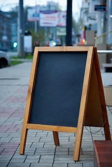 Placa de publicidade em branco na rua da cidade no fundo desfocado.