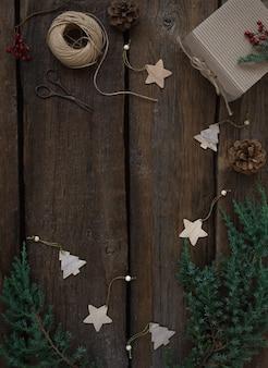 Placa de quadro de natal vintage de ramos de abeto, cones, caixa de presente, brinquedos de natal de madeira. fundo de madeira, cópia espaço. conceito de natal.