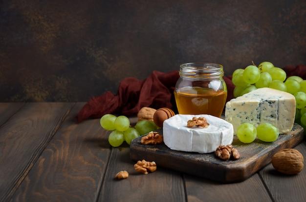 Placa de queijo com uvas, mel e porcas no fundo escuro.