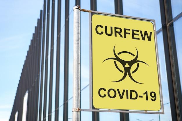 Placa de rua com inscrição toque de recolher com um ícone de vírus covid-19