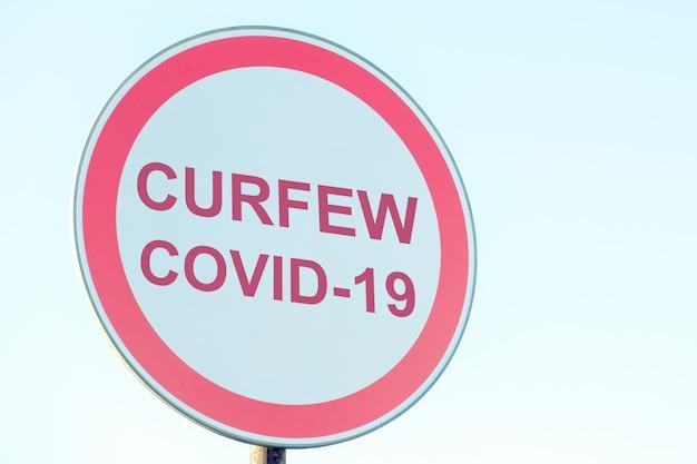Placa de rua com toque de recolher, vírus covid-19.