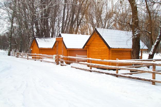 Placa de sinal e nova casa de madeira amarela na floresta de inverno