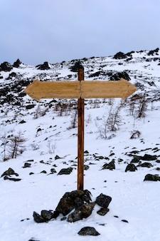 Placa de sinalização bidirecional sem inscrições em uma paisagem montanhosa deserta de inverno