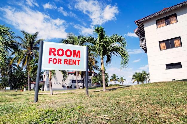 Placa de sinalização com o texto room for rent perto de um edifício moderno na zona rural. alugue casas e quartos em uma bela área de resort perto da costa