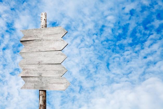 Placa de sinalização de madeira em um fundo de céu azul com nuvens