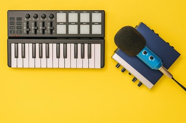Placa de som, mixer de música e microfone em fundo amarelo. o conceito de organização do local de trabalho. equipamentos para gravação, comunicação e escuta musical.