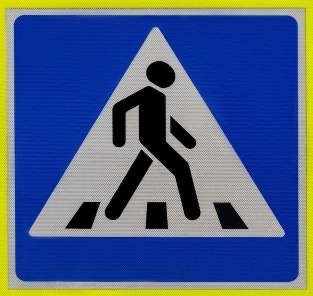 Placa de trânsito de uma passagem de pedestres homem andando sobre uma zebra em um triângulo sobre um fundo azul