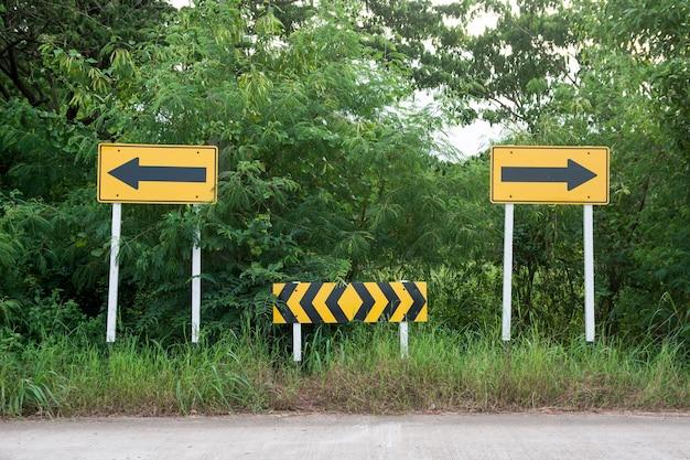 Placa de trânsito. sinais de seta amarela no final da estrada, apontando para a esquerda e para a direita