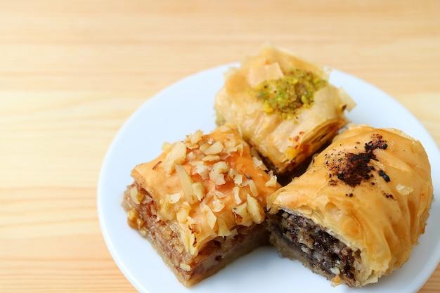 Placa de três tipos de doces baklava servidos na mesa de madeira, foco seletivo com espaço livre para texto e design