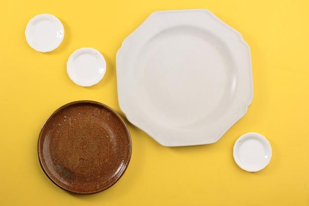 Placa de vários tamanhos de vista superior para adereços de alimentos, conceito de prato vazio sobre fundo amarelo. copie o espaço para design, propaganda e receita
