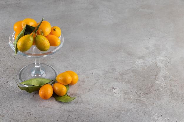 Placa de vidro de kumquats suculentos frescos em fundo de pedra.