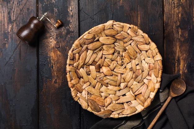 Placa de vime marrom e colher de pau em fundo de madeira velho. configuração da tabela.