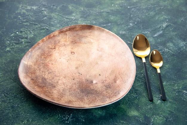 Placa de vista frontal marrom com colheres de ouro em fundo escuro