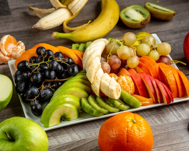 Placa de vista lateral com frutas fatiadas banana uvas maçã kiwi laranja