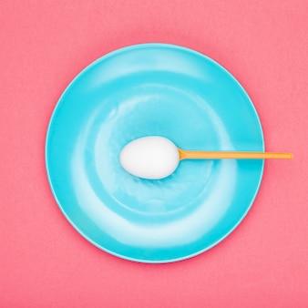 Placa de vista superior com colher segurando ovo