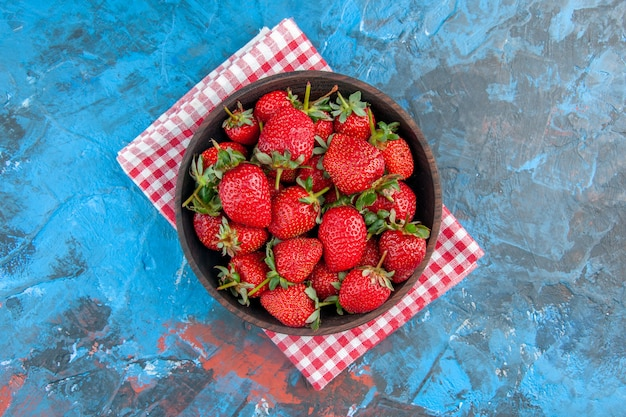 Placa de vista superior com saborosas frutas maduras frescas de morangos sobre fundo azul