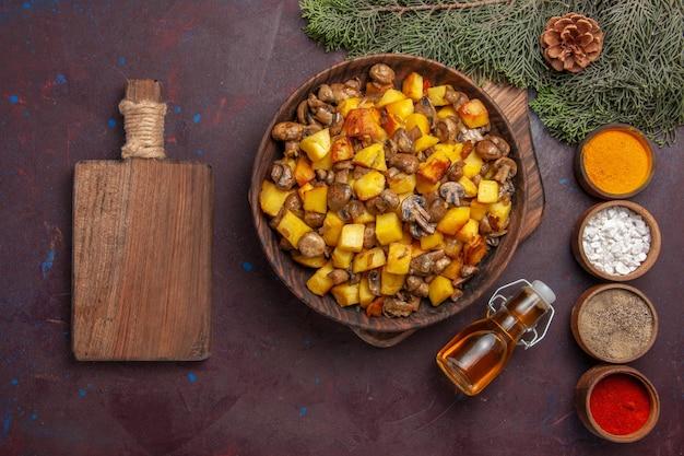 Placa de vista superior com tigela de madeira para alimentos com cogumelos fritos e batatas, tábua de cortar temperos coloridos e óleo ao lado dos galhos com cones
