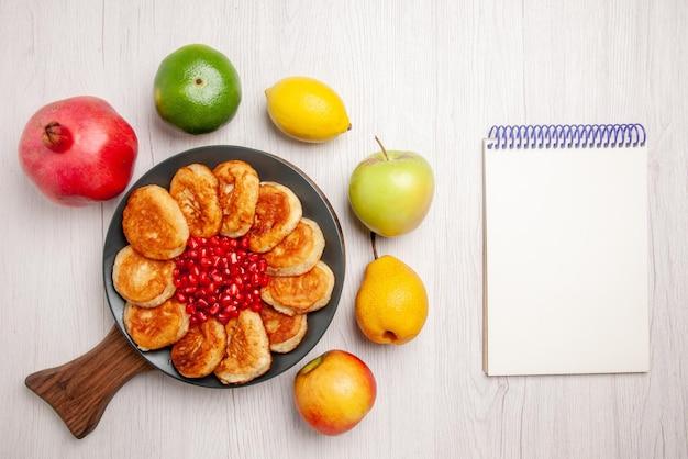 Placa de vista superior na placa de panquecas e romã na placa de madeira e romã maçã pêra limão e lima em torno dela ao lado do caderno branco sobre a mesa