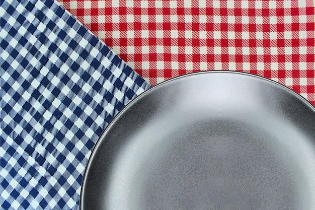 Placa de vista superior na toalha de mesa quadriculada