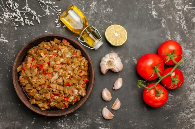 Placa de visualização de close-up superior de feijão verde garrafa de óleo alho limão ao lado de tomates vermelhos maduros com placa de pedicelo de feijão verde e tomate na mesa
