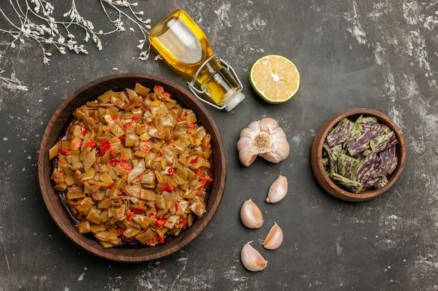 Placa de visualização de close-up superior de placa de feijão verde de feijão verde e tomate ao lado da garrafa de óleo de alho e limão na mesa