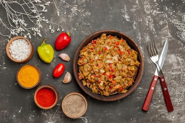 Placa de visualização de close-up superior na mesa prato apetitoso de feijão verde ao lado das tigelas de especiarias coloridas, tomate, alho, bola, pimenta, garfo e faca, na mesa escura